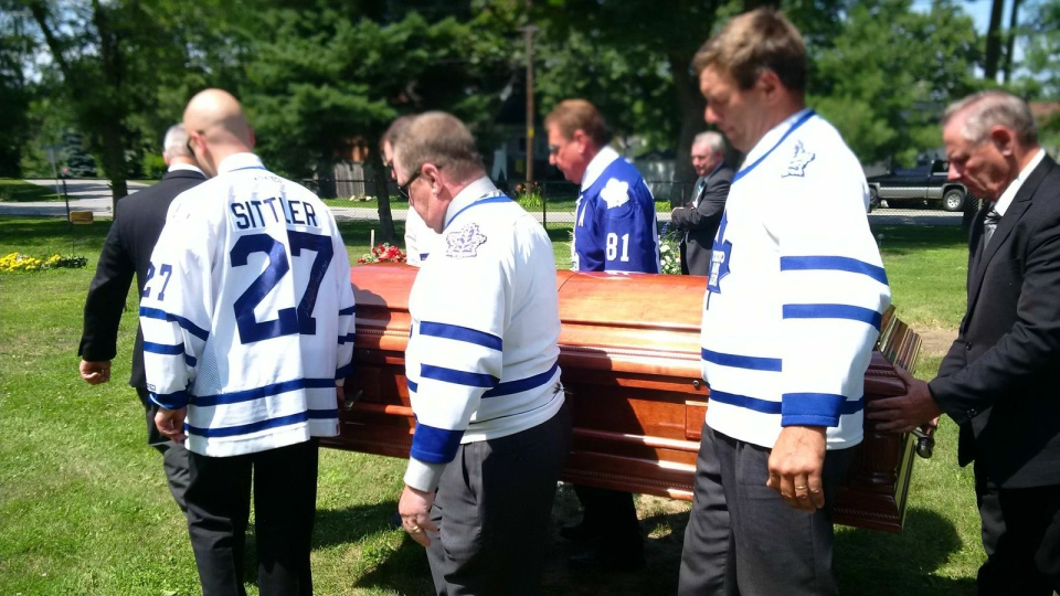 Pallbearers wearing Toronto Maple Leafs jerseys carry the casket of Terrance Warren Siebert.