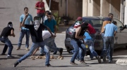 Palestinian protesters hurl stones at Israeli soldiers during clashes with Israeli soldiers following a protest against the Israeli military action in Gaza, at an area near the Beit El Jewish settlement and the West Bank city of Ramallah, Friday, July 25, 2014. (AP / Majdi Mohammed)