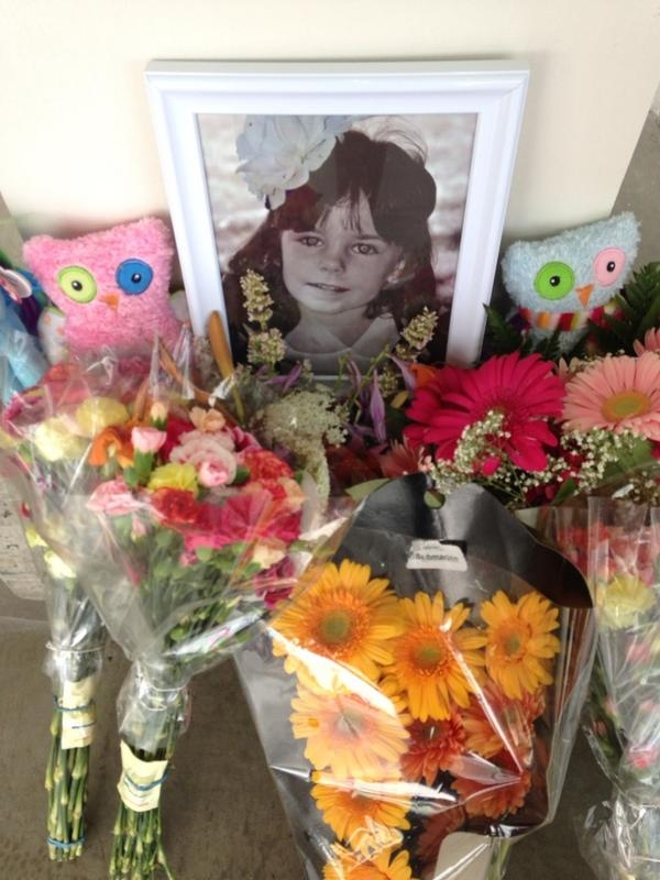 Flowers and stuffed toys are left at the scene of an accident that injured six people at Costco in London on July 25, 2014.