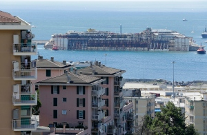 The wreck of the Costa Concordia cruise ship is towed by tugboats towards Genoa's harbor, Italy, Sunday, July 27, 2014. (AP / Antonio Calanni)