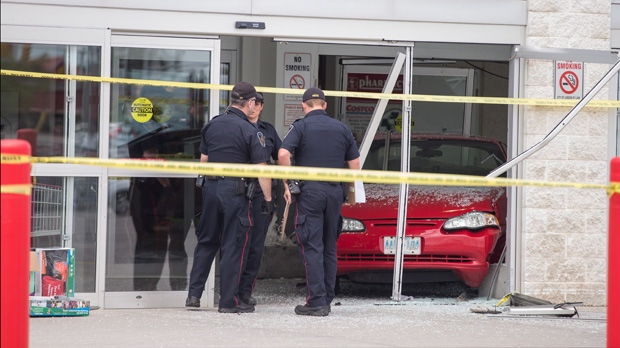 Police investigate after a car backed through the entrance of Costco in London, Ont., on Friday, July 25, 2014. (Geoff Robins / THE CANADIAN PRESS)