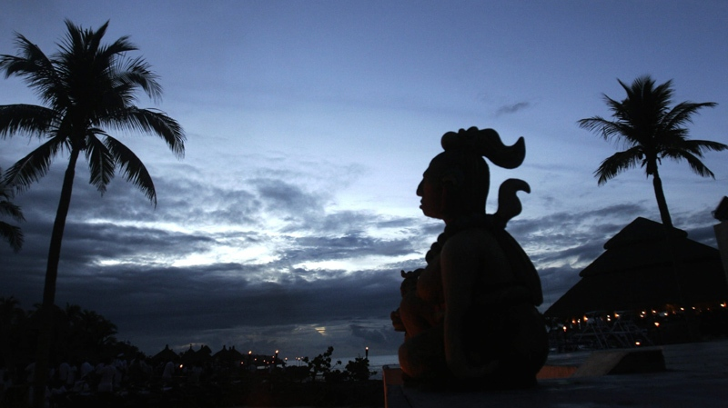 This June 1, 2007 file photo shows a Mayan statue stands in Playa Del Carmen, Mexico, where people will gather before making their way across the Yucatan Channel, to the Cozumel Island, in a ten mile pilgrimage in honor of the Mayan goddess Ixchel. Only a year is left before Dec. 21, 2012, when some believe the Maya predicted the end of the world.