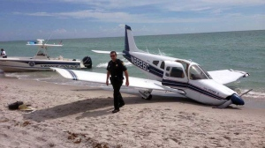 Emergency personnel at the scene of a small plane crash in Caspersen Beach in Venice, Fla., Sunday, July 27, 2014. Authorities say a father was killed and his daughter seriously injured while walking on the sand when a small plane crash landed along Florida's Gulf Coast near Venice Beach. (AP Photo/Sarasota County Sheriff's Office)