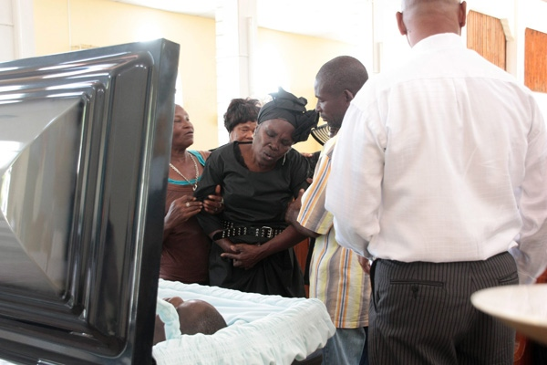 Oscar Bartholomew's mother Andrianne, 71, is restrained at her son's casket during his funeral Monday, Jan. 9, 2012 in Crochu, Grenada. (THE CANADIAN PRESS/Colin Perkel)
