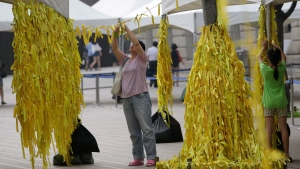 A mother and her daughter tie yellow ribbons with messages for missing passengers and victims aboard the sunken ferry Sewol in the water off the southern coast, at a group memorial altar in Seoul, South Korea, Monday, July 28, 2014. (AP / Lee Jin-man)