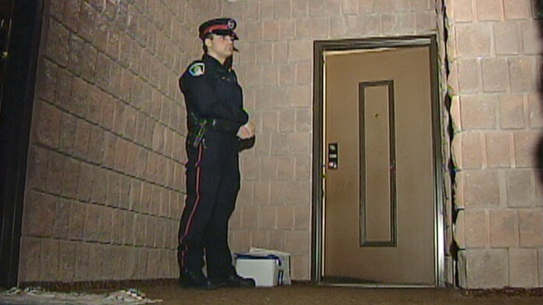 A Waterloo Regional Police Service officer stands outside the Green Valley Drive apartment of Larry McDonald in Kitchener, Ont. in March 2010.