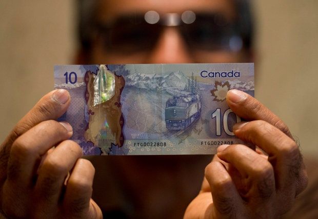 Hitesh Doshi poses with a $10 Canadian bank note