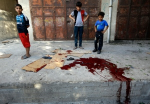 Palestinians look at a pool of blood from victims of an explosion that killed 10 people, 9 of them children, at a park at Shati refugee camp, in the northern Gaza Strip, Monday, July 28, 2014. (AP / Lefteris Pitarakis)