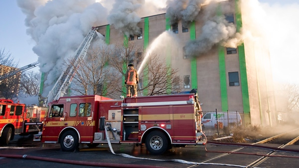 Toronto firefighters pulled out of the building when growing flames threatened rescue workers Monday, Jan. 9, 2012. (Tom Stefenac / CTV News)