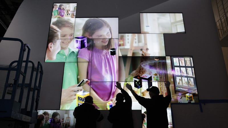 Workers set up a flat screen display at the Samsung exhibit for the Consumer Electronics Show, Monday, Jan. 9, 2012, in Las Vegas. (AP Photo/Julie Jacobson)