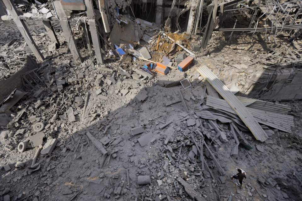 A Palestinian from a neighboring apartment building carries out debris as he walks on the rubble of the offices of the Hamas movement's Al-Aqsa satellite TV station, in Gaza City, northern Gaza Strip, destroyed by an Israeli strike, Tuesday, July 29, 2014. (AP / Lefteris Pitarakis)