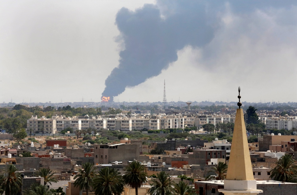 Black smoke billows over the skyline as a fire at the oil depot for the airport rages out of control after being struck in the crossfire of warring militias battling for control of the airfield, in Tripoli, Libya Monday, July 28, 2014. (AP / Mohammed Ben Khalifa)