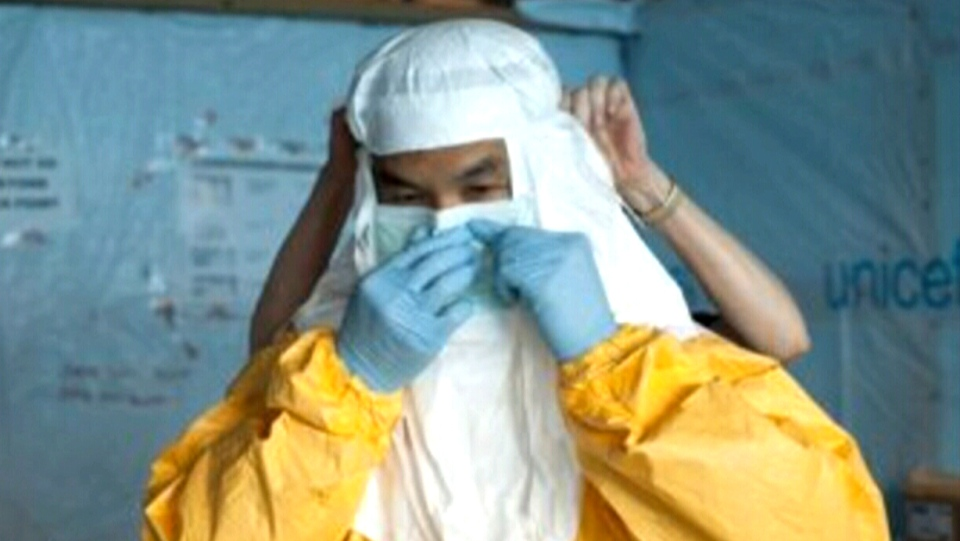 Dr. Azaria Marthyman of Victoria, B.C. is seen putting on protective gear before treating Ebola patients in Liberia.