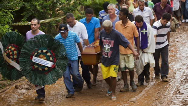 Relatives carry the coffins of a family that was killed by a mudslide to the cemetery in Jamapara, Rio de Janeiro state, Brazil, Tuesday Jan. 10, 2012.