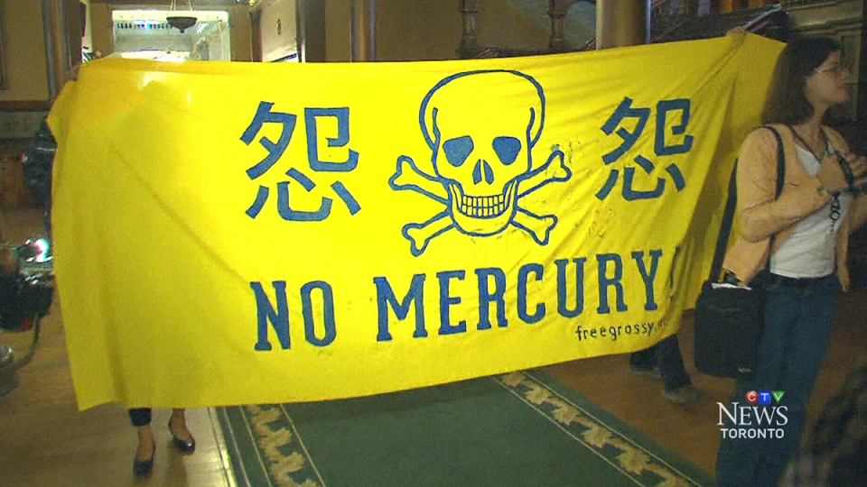 Protesters hold a sign related to the mercury-related health issues of Grassy Narrows First Nation residents, at Queen's Park in Toronto, Tuesday, July 29, 2014.