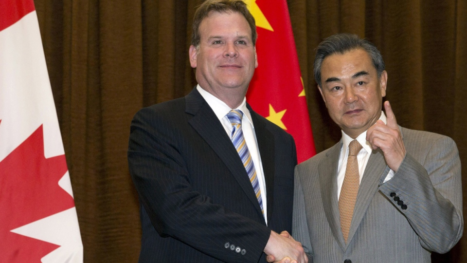 Foreign Affairs Minister John Baird, left, poses with his Chinese counterpart Wang Yi for photographers before a meeting at the Foreign Ministry in Beijing Tuesday, July 29, 2014. (AP / Ng Han Guan)