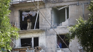 A man leans out to take a photo from a damaged residential apartment house after shelling in Donetsk, eastern Ukraine, Tuesday, July 29, 2014. (AP / Dmitry Lovetsky)