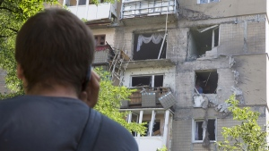 A man speaks on a mobile phone near to a damaged residential apartment house after the shelling in Donetsk, eastern Ukraine Tuesday, July 29, 2014. (AP / Dmitry Lovetsky)