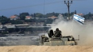 An Israeli armored vehicle stirs up dust near the Israel Gaza border, Tuesday, July 29, 2014. (AP / Tsafrir Abayov)