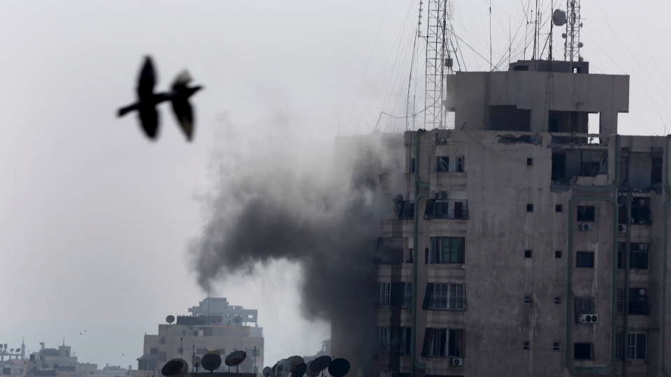 Smoke rises from Al Dawod tower apartment damaged by an Israeli strike in Gaza City in the northern Gaza Strip on Wednesday, July 30, 2014. (AP / Adel Hana)
