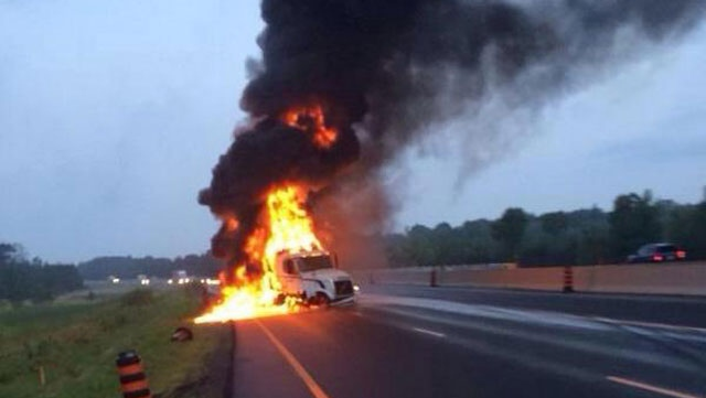A Tractor-trailer on fire closes Highway 401 east of Belleville on Wednesday, July 30, 2014. (Brian Jones/Twitter: @Highway_Life)
