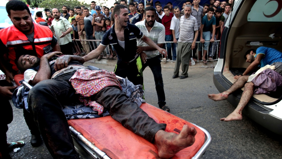 Palestinians carry a man injured from a strike in Shijaiyah neighbourhood, to the emergency room of Shifa Hospital, in Gaza City, Wednesday, July 30, 2014. (AP / Khalil Hamra)
