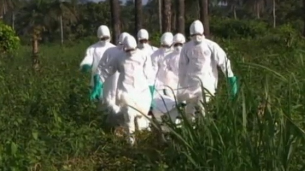 Workers in hazardous material suits transport the body of an unidentified person claimed by the Ebola virus in Liberia