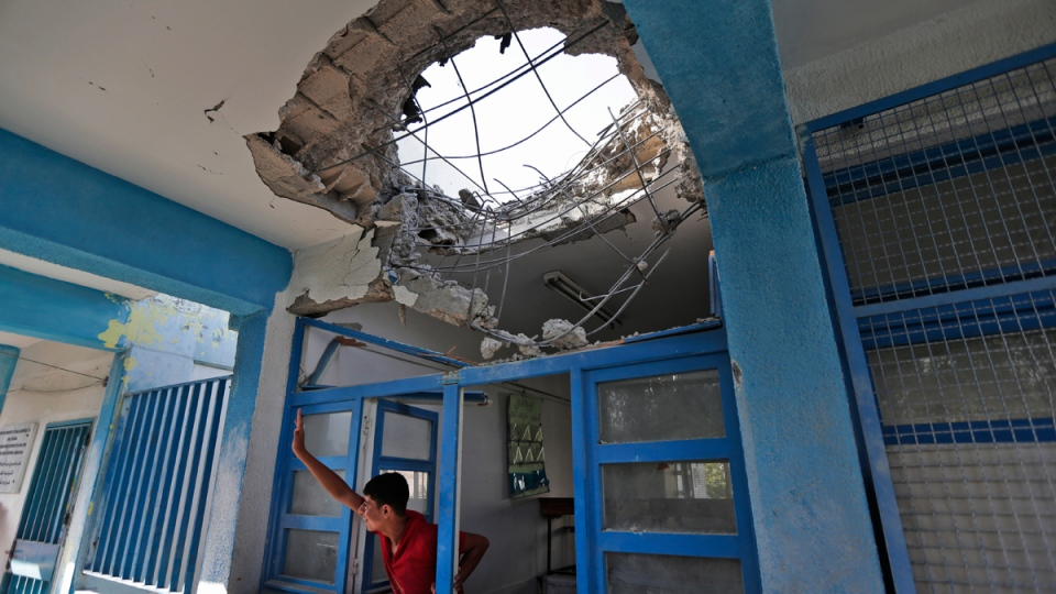 A displaced Palestinian child waves to a friend from inside a damaged classroom at the Abu Hussein UN school, in Jabalya refugee camp, northern Gaza Strip, hit by an Israeli strike earlier, on Wednesday, July 30, 2014. (AP / Lefteris Pitarakis)