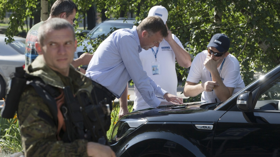 Alexander Hug, deputy head of the OSCE mission to Ukraine, centre, and his colleagues examine a map as they discuss the situation around the site of the crashed Malaysia Airlines Flight 17, in the city of Donetsk, eastern Ukraine, Wednesday, July 30, 2014. (AP / Dmitry Lovetsky)