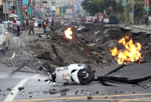 Vehicles are left lying on a destroyed street as part of the street is burning with flame following multiple explosions from an underground gas leak in Kaohsiung, Taiwan, early Friday, Aug. 1, 2014. (AP) TAIWAN OUT