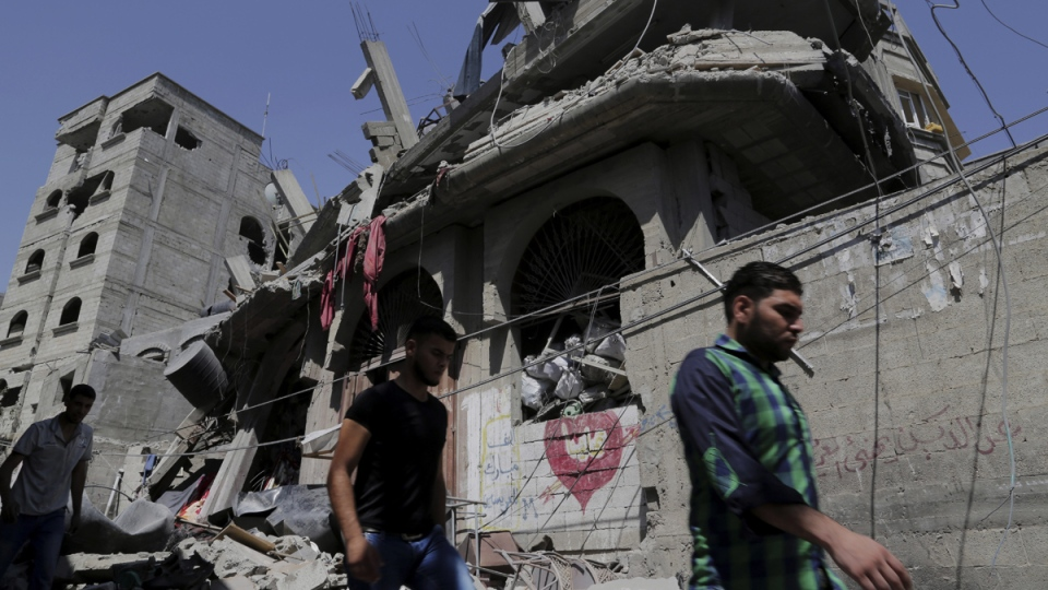 Palestinians walk on the rubble of a destroyed house in an Israeli attack in the Bureij refugee camp in the central Gaza Strip on Friday, Aug. 1, 2014. (AP / Adel Hana)