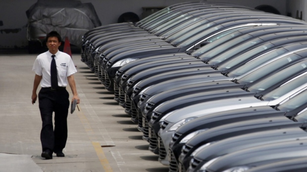 A man walks past brand new cars at a car dealer in Shanghai, China, Wednesday June 8, 2011. (AP Photo/Eugene Hoshiko)