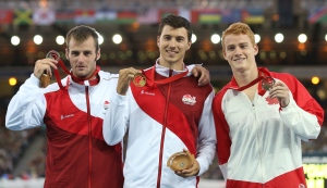 Canadian Shawnacy Barber stands on the right with the bronze medal he won in pole vault during the 2014 Commonwealth Games in Glasgow, Scotland, on Aug. 1, 2014. (AP/Scott Heppell)