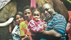 In this undated family file photo provided by the National Action Network, Saturday, July 19, 2014, Eric Garner, right, poses with his children during a family outing. New York City officials said Wednesday they are trying to negotiate a settlement with Garner's family. (AP Photo/Family photo via National Action Network, File)