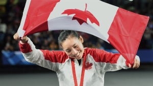 Canada's Michelle Li displays her gold medal after defeating Scotland's Kirsty Gilmour in badminton action at the Commonwealth Games in Glasgow, Scotland on Sunday, August 3, 2014. (Andrew Vaughan / THE CANADIAN PRESS)