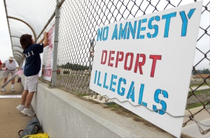 Michelle Pescscott hangs political signs during a protest against people who immigrate illegally, on July 19, 2014, in Conroe, Texas. (AP/Conroe Courier, Jason Fochtman)