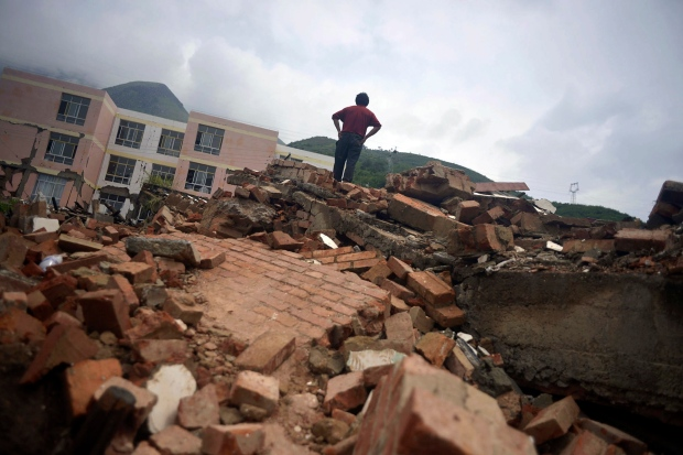 A resident stands on remnants of a collapsed building at the epicenter of an earthquake that struck the town of Longtoushan in Ludian county in southwest China's Yunnan province Monday, Aug. 4, 2014. (AP Photo)