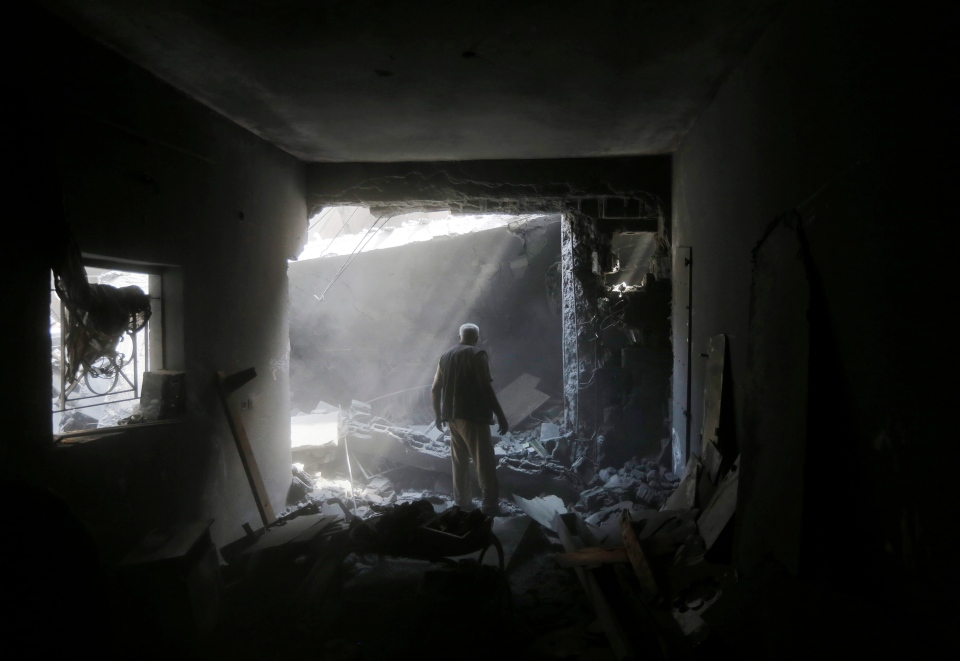 A member of the Shabat family inspects the damage upon returning to the family house, destroyed by Israeli strikes in the town of Beit Hanoun, northern Gaza Strip, Tuesday, Aug. 5, 2014. (AP / Lefteris Pitarakis)