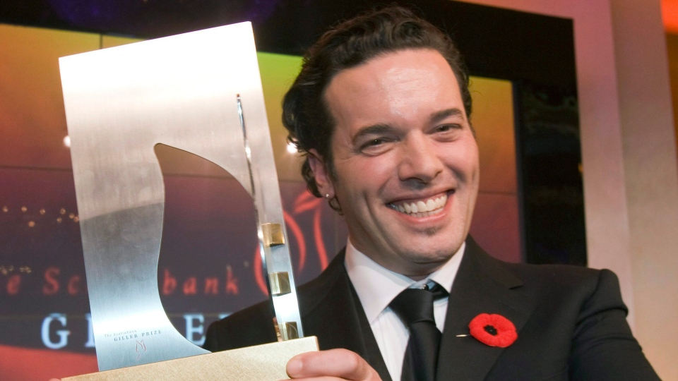 Joseph Boyden holds the Giller Prize after winning it in Toronto on Tuesday, November 11, 2008. (Frank Gunn / THE CANADIAN PRESS)