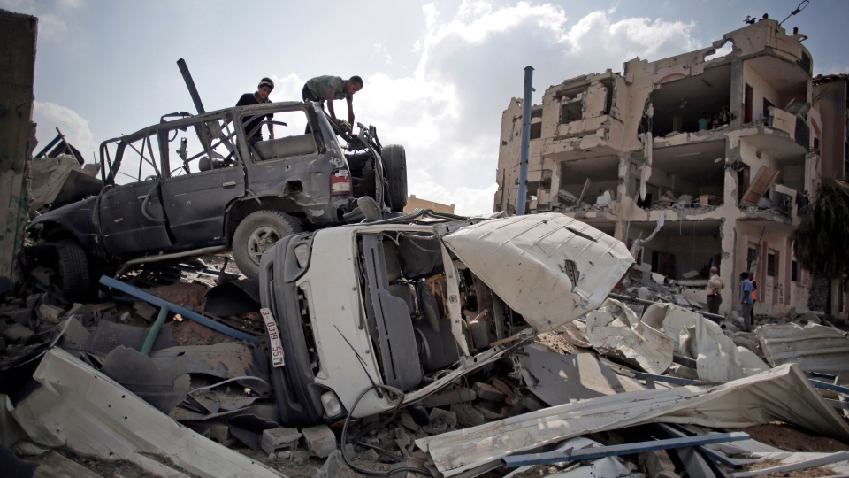 Palestinians search destroyed cars in Rafah's district of Shawkah in the southern Gaza Strip, Tuesday, Aug. 5, 2014. (AP / Khalil Hamra)