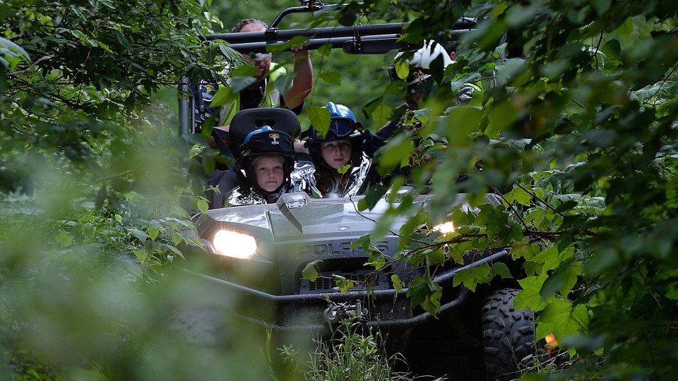 Paramedics transport two young girls near Aird Lake, Ont., on Tuesday, Aug. 5, 2014., after they went missing late evening Monday Aug. 4 while playing a game of hide-and-seek. (Sean Kilpatrick / THE CANADIAN PRESS)