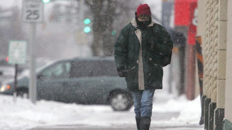 A pedestrian makes her way down Lincoln Way N battling the snow and bitter cold Friday, Jan. 13, 2012, in LaPorte, Ind. (AP Photo/The News Dispatch, Bob Wellinski)