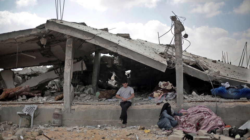 A Palestinian sits in front of a destroyed house in Rafah's district of Shawkah in the southern Gaza Strip, Tuesday, Aug. 5, 2014. (AP / Khalil Hamra)