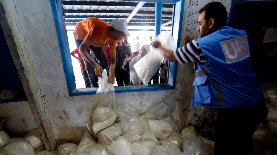 Palestinians crowd a window for food aid at a United Nations distribution center in the Shati refugee camp in Gaza City, Wednesday, Aug. 6, 2014. (AP / Hatem Moussa)