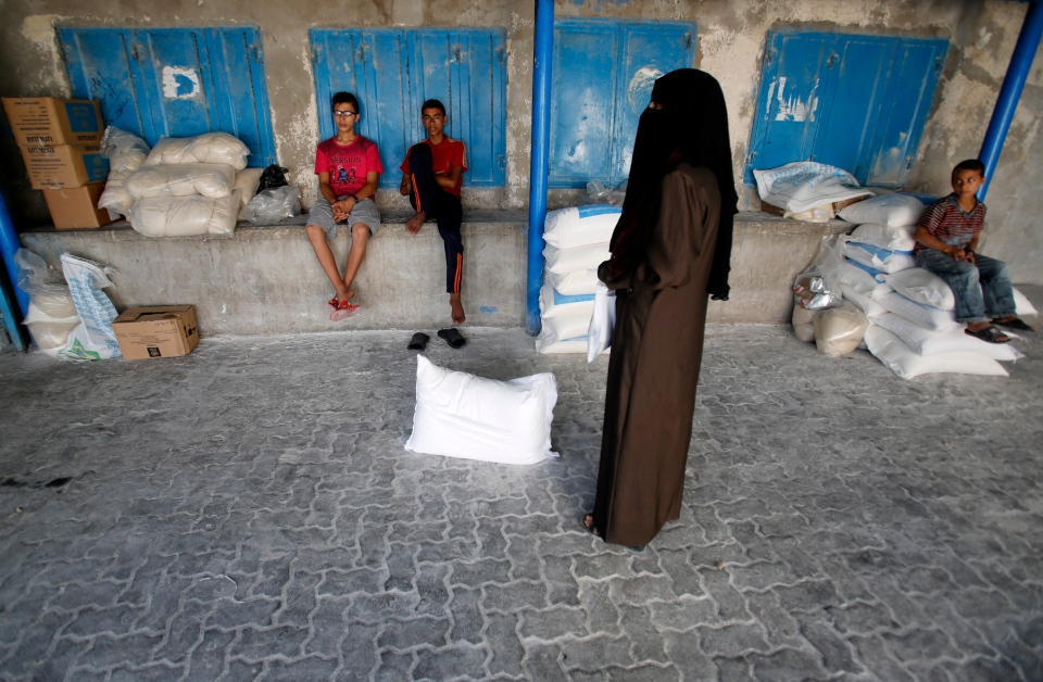 Palestinians stand by bags of flour at a United Nations food aid distribution centre, in the Shati refugee camp in Gaza City, Wednesday, Aug. 6, 2014. (AP / Hatem Moussa)