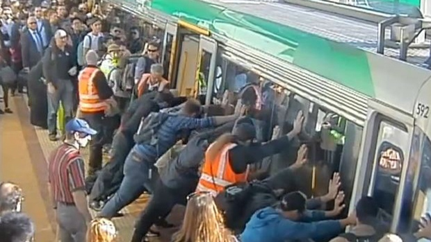 Dozens of people in Perth, Australia push a commuter train car in order to help free a man whose foot was stuck in the gap between the station platform and train. (Public Transport Authority of Western Australia)