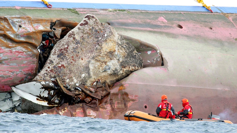 Firefighters on a dinghy look at a rock emerging from the side of the luxury cruise ship Costa Concordia, the day after it ran aground off the Tuscan island of Giglio, Italy, Sunday, Jan. 15, 2012. (AP / Andrea Sinibaldi, Lapresse)
