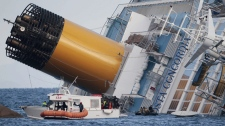 Italian firefighters conduct search operations on the luxury cruise ship Costa Concordia that ran aground the tiny Tuscan island of Isola del Giglio, Italy, Sunday, Jan. 15, 2012. (AP Photo/Gregorio Borgia)