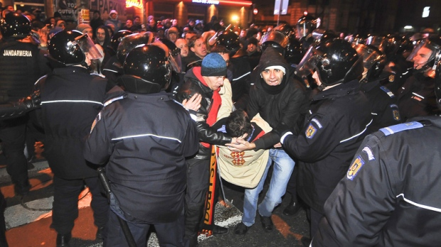 Protesters evacuate an injured person during clashes with Romanian riot police in University Square, the scene of the first anti-communist protest in 1989, in Bucharest, Romania, early Sunday morning, Jan. 15, 2012. (AP / Octav Ganea)