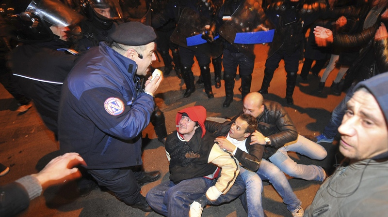 Protesters sit on the pavement surrounded by Romanian riot police in University Square, the scene of the first anti-communist protest in 1989, in Bucharest, Romania, early Sunday morning, Jan. 15, 2012. (AP Photo/Octav Ganea)